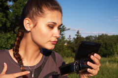 Girl watches herserf in portable Stock Photo