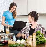 Girl watches the recipe on laptop Royalty Free Stock Photo