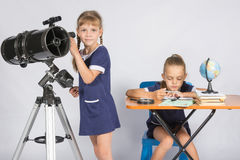Girl watches in the telescope, the other girl is waiting for the results of observations Royalty Free Stock Image