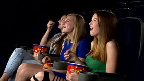Girl watching саmedy film at the cinema, eating
