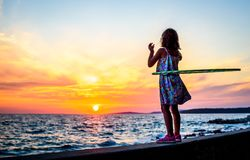 Girl is watching amazing sea sunset with hula hoop royalty free stock images
