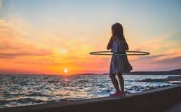 Girl is watching amazing sea sunset with hula hoop stock image
