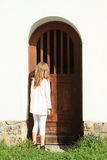 Girl watching behind door Stock Photo