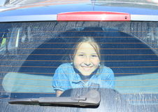 Girl watching from car trunk Stock Images