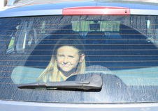 Girl watching from car trunk Stock Image