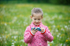 Girl watching cartoon and playing games on smartphone Royalty Free Stock Images