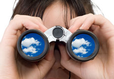 Girl Watching Clouds. A young girl watching some clouds with a set of binoculars Stock Photography