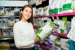 Girl watching dry food in pet store Stock Images