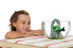 Girl is watching fish in an aquarium Stock Photos