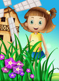 A girl watching the flowers in the garden near the windmill Stock Photos