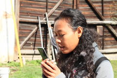 Girl watching hand phone. Tropical girl - young Papuan woman with curly black hair watching her smartphone Royalty Free Stock Photos