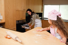 Girl watching her mother putting cookies into the oven Royalty Free Stock Photo