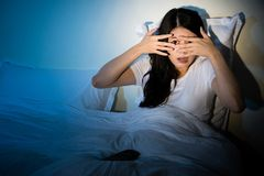 Girl watching horror movie cove her eyes. Young girl sitting on a bed watching a horror movie scary to cove her eyes on TV. mixed race asian chinese model Royalty Free Stock Photos