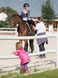 Girl watching horse rider Royalty Free Stock Photo
