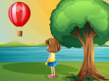 A girl watching the hot air balloon at the riverbank Stock Photo