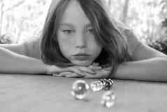 Girl watching marble game stock image