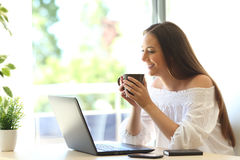 Girl watching media in a laptop at home Stock Photos