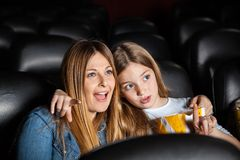 Girl Watching Movie With Shocked Mother In Theater. Cute girl showing something to shocked mother while watching movie in cinema theater Royalty Free Stock Photography