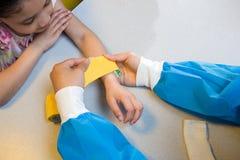 Girl watching nurse put bandage on her arm Stock Image