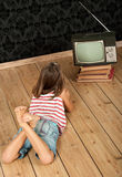 Girl watching old tv Royalty Free Stock Photography