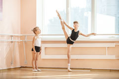 Girl watching older ballet student practicing at barre. Little girl watching older ballet student practicing at barre Royalty Free Stock Image