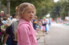 Girl Watching Parade. A young girl enjoys watching a parade with others in the crowd as the parade rolls down the street stock image