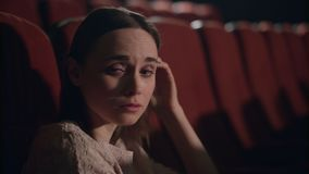 Girl watching sad film at movie theater. Woman crying on melodrama stock footage