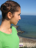 Girl watching the sea. Girl in green T-shirt watching the sea Royalty Free Stock Photo