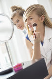 Girl watching sister applying makeup in front of mirror at home Royalty Free Stock Photos