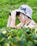 Girl watching someone through binoculars from behind bushes Stock Photo