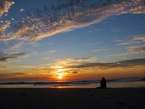 A girl watching  sunrise on the beach Stock Photos