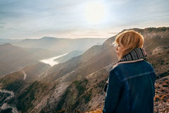 Girl watching sunset. Beautiful girl on top of mountain watching sunrise Stock Images