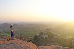 A girl is watching the sunset in Hampi. The girl stands on top of the mountain and looks into the distance. Meditation, harmony,. Alone with nature, silence stock photo