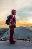 Girl watching at the sunset on the top of mountain Stock Photo