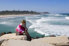 Girl watching surfers Royalty Free Stock Photography