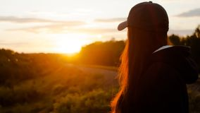 Girl watching to the sunset. Girl watching to the warm sunset on the railway stock images