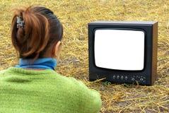 Girl watching TV. In meadow. Element of design Stock Photo