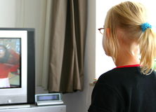 Girl watching tv. Blonde girl with pony tail and glasses seen on the back watching tv Stock Images