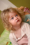 Girl watching tv. Two year old girl watching television with serious face expression Royalty Free Stock Photo