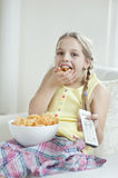 Girl watching TV as she stuffs her mouth with wheel shape snack pellets Royalty Free Stock Photography