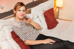 Girl Watching TV in Bed. Young pretty girl holding a remote and watching TV in bed Stock Photography