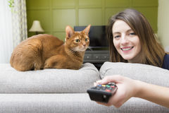 Girl watching tv with cat Stock Images