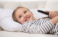 Girl watching TV. Cheerful little girl holding remote control and smiling Stock Photo