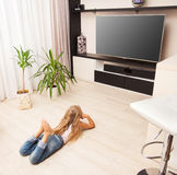 Girl watching TV. Child laying on the floor and watching TV at home Stock Photo