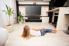 Girl watching TV. Child laying on the floor and watching TV at home Royalty Free Stock Photo