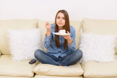 Girl watching TV and eating on sofa Royalty Free Stock Image