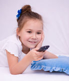 Girl watching tv. Happy girl watching tv, remote control Royalty Free Stock Image