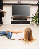 Girl watching TV at home Stock Images
