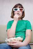 Girl watching TV movies in 3D stereo glasses. Girl watching TV movies in anaglyph stereo glasses and eating popcorn royalty free stock image