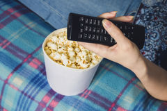 Girl watching tv with popcorn at home in the living room. The concept of laziness Stock Photo